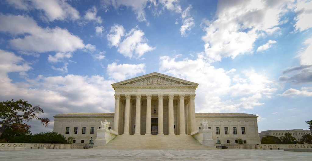 The United States Supreme Court Building in Washington DC. Surprisingly void of people, this image shows the entire building set under a partially cloudy sky.